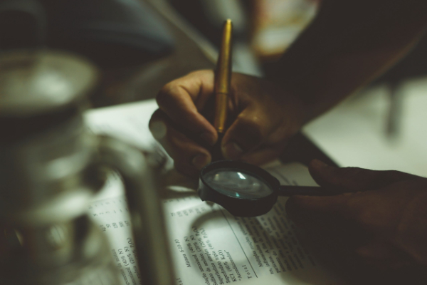 Hands conducting an audit with magnifying glass